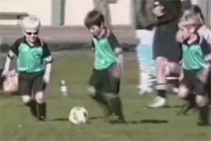 A young boy with albinism plays soccer with his teammates.