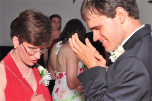 A teenage couple dances at a prom.