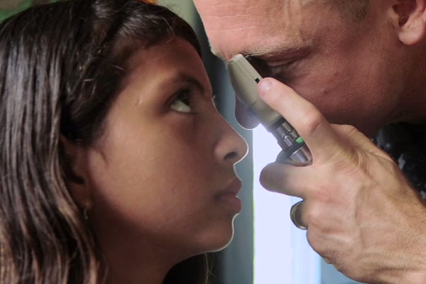 An adolescent girl receiving an eye exam.