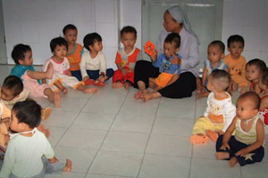 A group of preschool chidren stting on tiled floor with a woman's wearing a nun's headpiece.