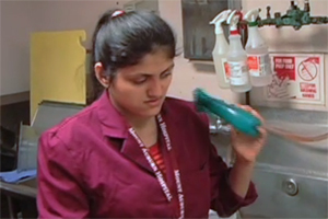 A young woman stands by an industrial sink and fills a plastic bottle with cleaning solution.