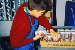 A boy wearing a blue apron prepares to place several cans of soda in a vending machine.