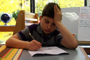 A boy works on his math worksheet.