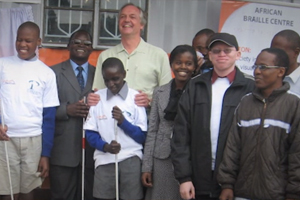 Group of blind students holding a white canes, standing outside the Perkins Brailler repair workshop in Nairobi, Kenya.