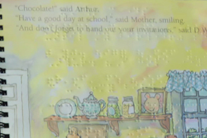 Colorful illustrations in an Arthur the Aardvark story with braille lettering is visible on the page.