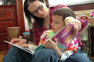 A young boy who is blind sits in his mother's lap as she reads him a children's book about our bodies.