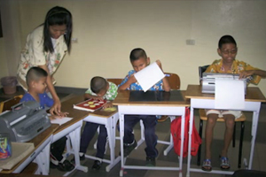 A group of young boys in Thailand using Perkins Brailler and reading braille.