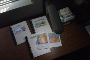 Colorfully illustrated children's books illuminated on a desk as an example of adapting environments for visually impaired students.