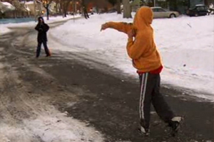 Two young boys in hooded sweatshirts play catch with a football in the middle of a snowy street.