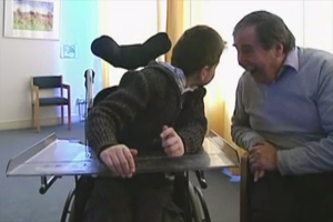 The young boy in the wheelchair turns his head to the left to face Dr. Van Dijk.