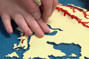 A young woman and a teacher are exploring a large tactile map of North America.