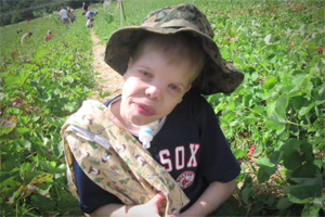 A young boy with Charge sitting in a strawberry field with this head tilted.