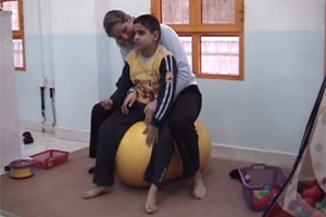 A teacher and a boy who is blind sit and bounce on a large, yellow exercise ball.