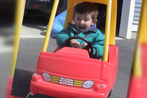 A young boy is playing in a large red and yellow toy car.