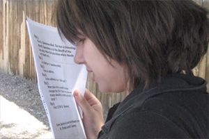 A young woman holding a page of directions close to her eyes as she reads an assignment.
