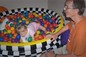 A girl with CHARGE crawling in an inflatable pool filled with colored plastic balls.