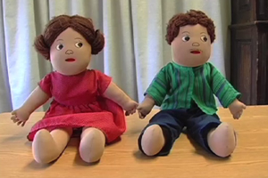 Two Teach-A-Bodies rag dolls are shown. The female doll wears a dress, and the male, pants and a shirt.