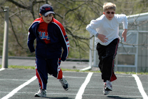 Two students running on a track field.