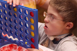 A young boy with CHARGE is playing the game Connect Four.