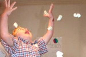 A young boy with CHARGE tossing handfuls of Styrofoam over his head.