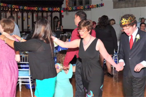 In a photograph taken at a prom, a group of dancers is in a conga line.