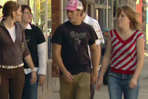 A group of teenagers, both boys and girls, conversing as they walk down a sidewalk.