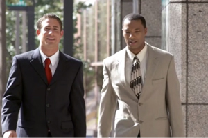 Two men in business suits hold a conversation while walking on the sidewalk.