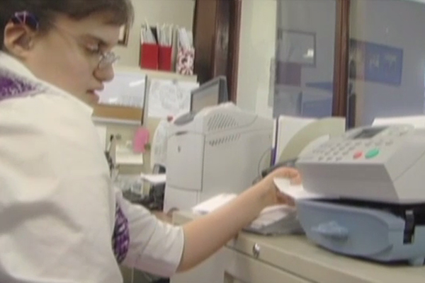 A young woman who is visually impaired runs the envelopes through the postage meter.