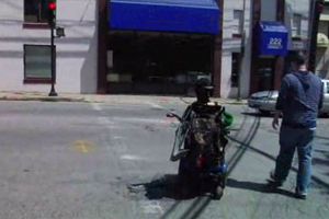 A young man in a motorized chair enter and cross the street, accompanied by an instructor.