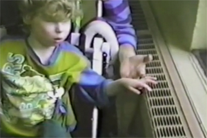 A boy being pushed in a wheelchair along the hallway and is encouraged to touch a radiator to feel the ridges.