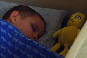 A young boy who is blind is sleeping with a yellow animal toy.