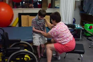 A young boy in a wheelchair is working with a physical therapist.