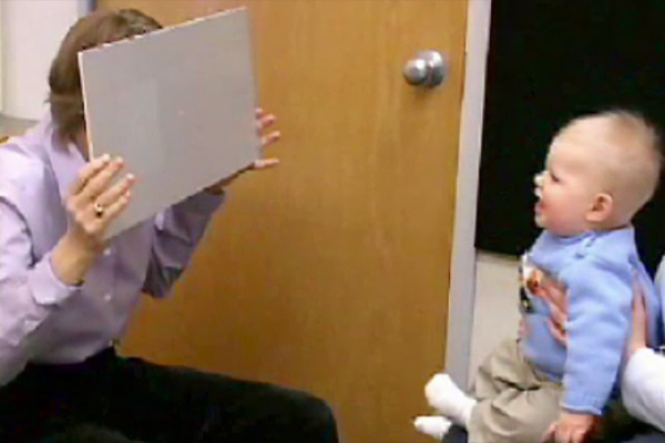 A demonstration of an acuity card test being administered to a very young boy.