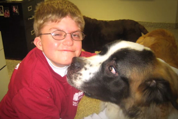 A young boy with CHARGE syndrome is hugging a large dog in the offices of an animal shelter where he works.