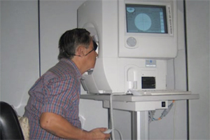 A patient seated at an automated static perimeter device to test for his sight.