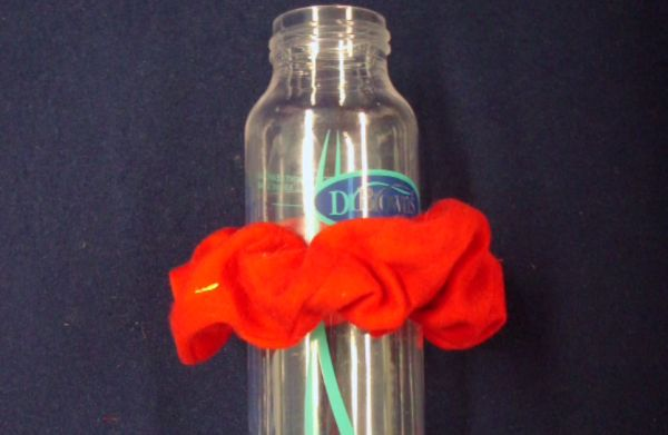 A child's bottle ringed by a bright red fabric.