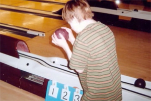 A young boy wearing a striped shirt preparing to roll the ball in a bowling alley.
