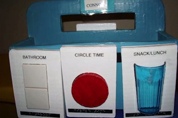 We see one example of a calendar system consisting of a box with a handle on which the name Connor is taped.