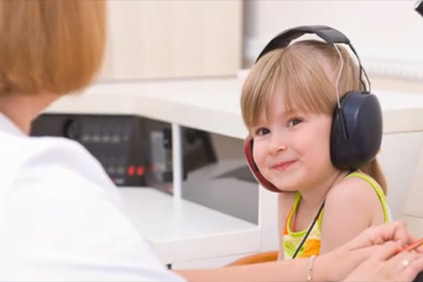 A young girl is shown wearing a large pair of headphones while taking a hearing test.