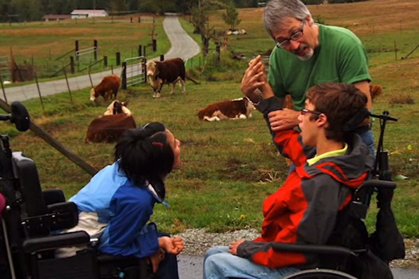 Several of the children in wheelchairs visiting with farm animals at a camp.