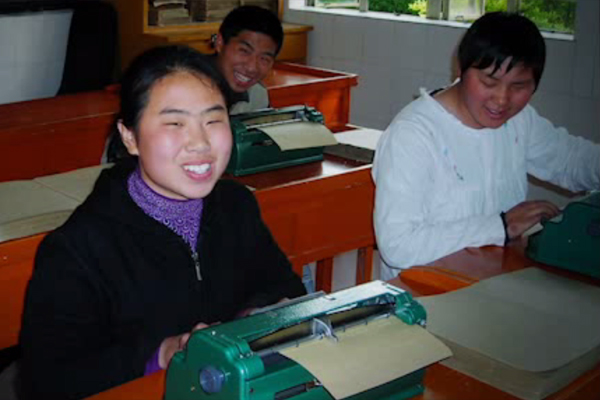 Group of blind students in a classroom at a school in China are creating pages of Braille on Perkins Braillers.