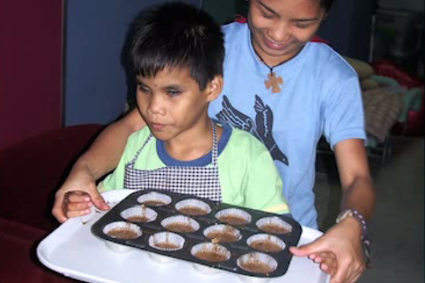 A young boy who is blind carrying a cupcake pan filled with batter.