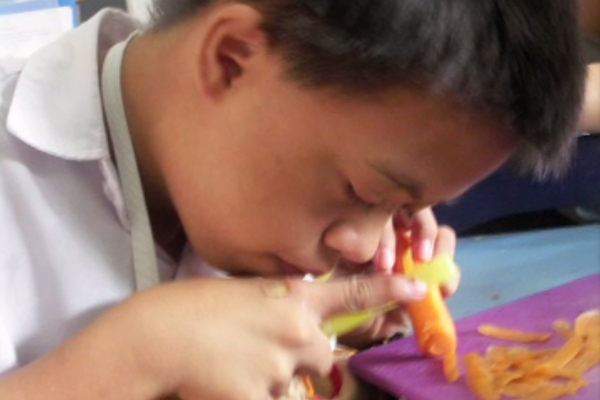 A boy who is blind holding a carrot and a vegetable peeler.