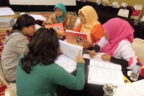 A group of teachers around a table discussing the curriculum guidelines.