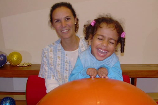 At an early intervention program in Uruguay, a young girl who is visually impaired laughs as she plays with a large orange exercise ball.