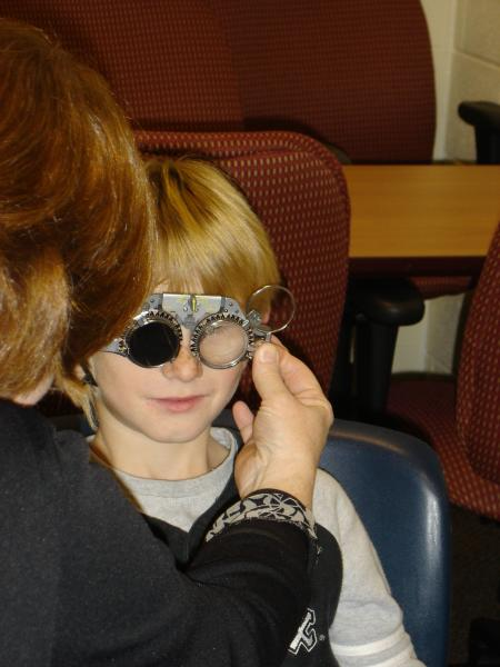 A young boy is having his eyes examined.