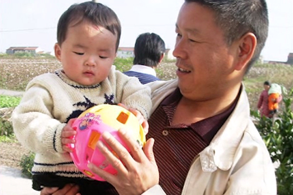 A father holds his young child, who is visually impaired.