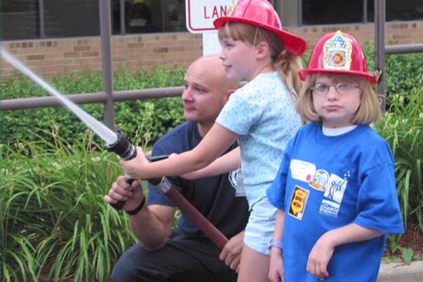 A young girl joins a firefighter holding a hose and spraying the water.