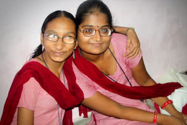 A photograph of two teenage girls sitting on the floor of a school in India.
