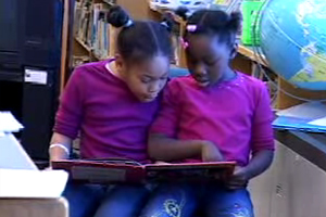 Two young girls reading a book.